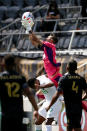 Los Angeles FC goalkeeper Pablo Sisniega (23) makes a save over Austin FC forward Danny Hoesen (9) during the first half of an MLS soccer match Saturday, April 17, 2021, in Los Angeles. (AP Photo/Ringo H.W. Chiu)