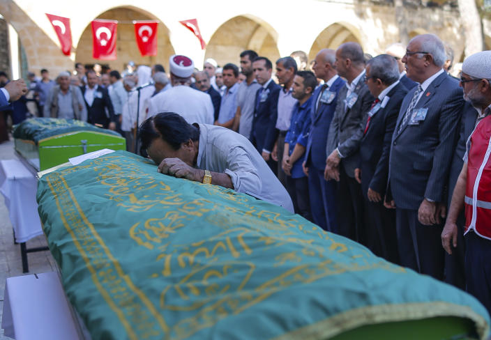 A mourner cries on the coffin of Halil Yagmur, 64, killed Friday during mortar shelling from Syria, during a funeral procession in the town of Suruc, southeastern Turkey, at the border with Syria, Saturday, Oct. 12, 2019. (AP Photo/Emrah Gurel)