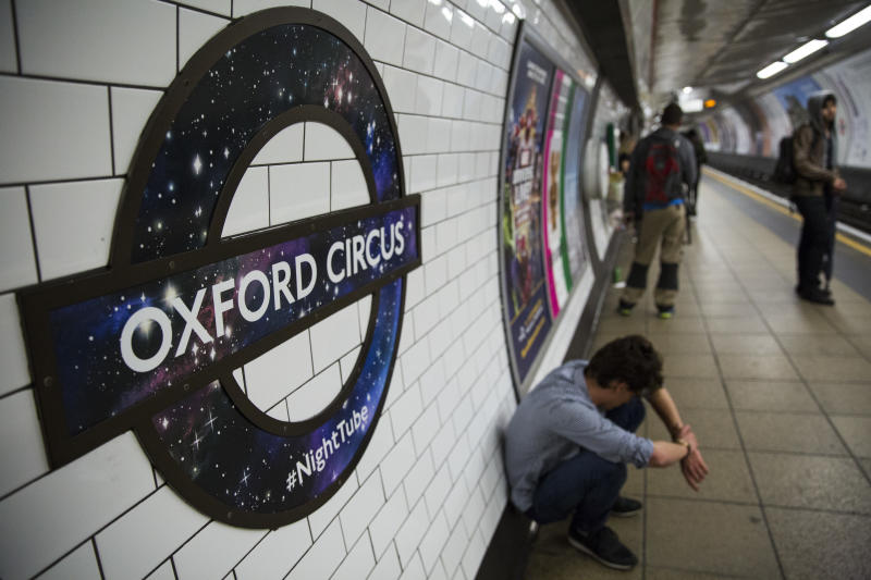 LONDON, ENGLAND - AUGUST 20: A man hunches down near a London Underground roundel redesigned for the launch of the Night Tube on display at Oxford Circus Underground station on August 20, 2016 in London, England. The London Underground's 24-hour service begins for the first time in its 153 year history. The new Night Tube will see both the Victoria and Central lines run through the night on Fridays and Saturdays. (Photo by Jack Taylor/Getty Images)