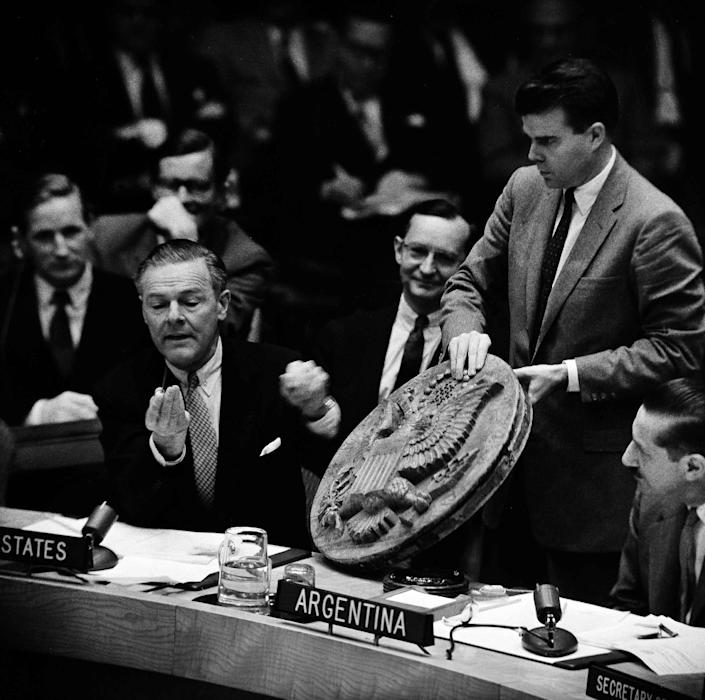 FILE - In this May 26, 1960 file photo, U.S. Ambassador to the U.N., Henry Cabot Lodge, assisted by Richard F. Pedersen, right, shows the Security Council at U.N. Headquarters a listening device which he said the Soviet authorities planted in the office of U.S. Ambassador Llewellyn Thompson in Moscow. The device, a wooden carving of the Great Seal of the United States, was hollow and contained a hidden microphone. It was presented to Lodge by a group of Russians. Israeli Prime Minister Benjamin Netanyahu's use of a cartoon-like drawing of a bomb to convey a message over Iran's disputed nuclear program this week, follows in a long and storied tradition of leaders and diplomats using props to make their points at the United Nations. (AP Photo/John Rooney, File)