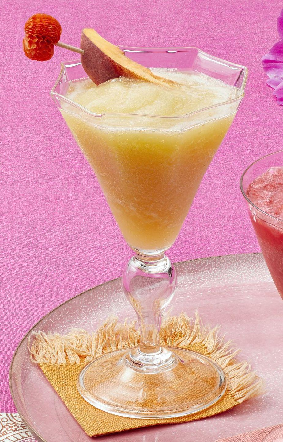 """<p>This frozen cocktail is like summer in a glass. It combines peaches, pineapple, and green grapes with orange-flavored vodka and white wine for a sweet and boozy drink.</p><p><a href=""""https://www.thepioneerwoman.com/food-cooking/recipes/a35995877/pineapple-peach-frozen-sangria-recipe/"""" rel=""""nofollow noopener"""" target=""""_blank"""" data-ylk=""""slk:Get Ree's recipe."""" class=""""link rapid-noclick-resp""""><strong>Get Ree's recipe. </strong></a></p><p><a class=""""link rapid-noclick-resp"""" href=""""https://go.redirectingat.com?id=74968X1596630&url=https%3A%2F%2Fwww.walmart.com%2Fsearch%2F%3Fquery%3Dblender&sref=https%3A%2F%2Fwww.thepioneerwoman.com%2Ffood-cooking%2Fmeals-menus%2Fg36432840%2Ffourth-of-july-drinks%2F"""" rel=""""nofollow noopener"""" target=""""_blank"""" data-ylk=""""slk:SHOP BLENDERS"""">SHOP BLENDERS</a></p>"""