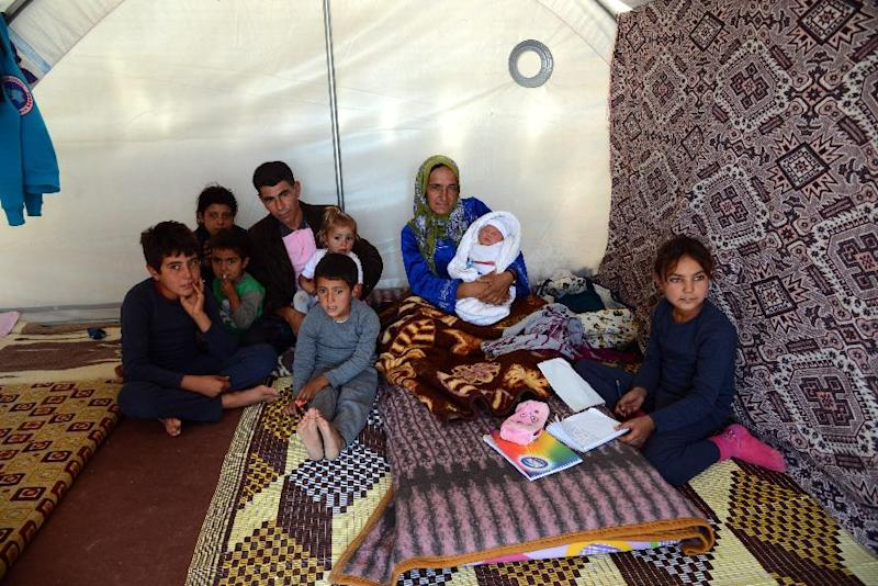 Sultan Muslim (3rd R) and her husband Mahmut Beko Muslim (4th L) pose with their children, including their newborn son Muhammed Obama Muslim, at Suruc Rojava refugee camp in Sanliurfa on October 22, 2014 (AFP Photo/Ilyas Akengin)
