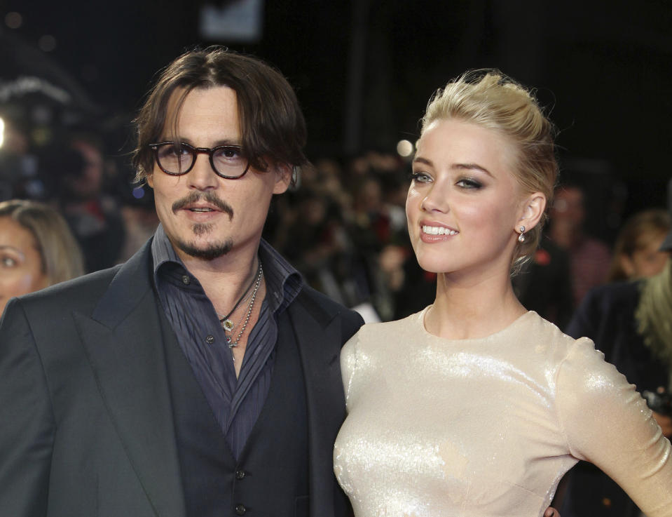 """FILE - In this Nov. 3, 2011 file photo, U.S. actors Johnny Depp, left, and Amber Heard arrive for the European premiere of their film, """"The Rum Diary,"""" in London. A Los Angeles judge finalized the actors' divorce, Friday, Jan. 13, 2017, after months of bickering over the final terms of their breakup, although the pair have agreed to honor the terms of a settlement that calls for Depp to pay Heard $7 million, which the actress has said she will donate to two charities. (AP Photo/Joel Ryan, File)"""