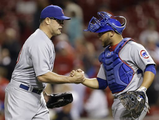 Chicago Cubs catcher Welington Castillo, right, congratulates relief pitcher Kevin Gregg after they defeated the Cincinnati Reds 4-2 in 10 innings of a baseball game, Tuesday, April 23, 2013, in Cincinnati. Gregg struck out two of the three batters he faced in the inning to earn his first save of the season. (AP Photo/Al Behrman)