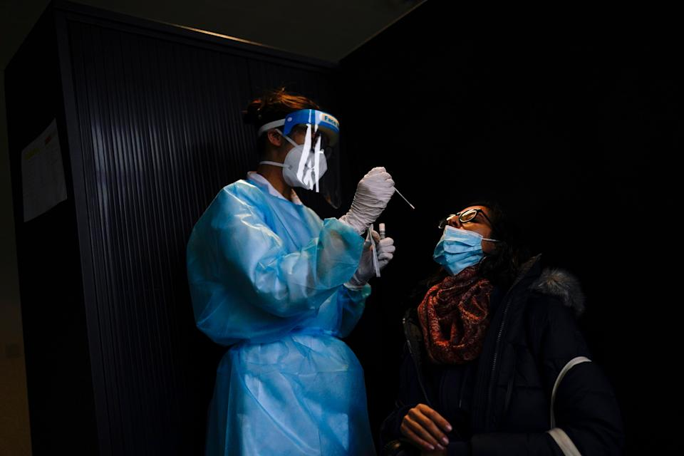 A medical worker, wearing full protective gear, takes a nose swab from a traveller, who arrived from UK, to be tested for Covid-19 at Gare du Midi international train station in Brussels (AP)