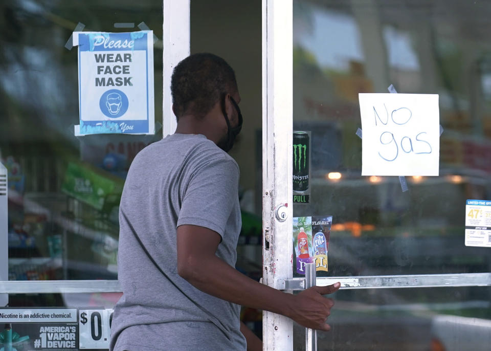A customer asks a Chevron gas station cashier when they expect gasoline to be delivered, Wednesday, May 12, 2021, in Miami. State and federal officials are scrambling to find alternate routes to deliver gasoline in the Southeast U.S. after a hack of the nation's largest fuel pipeline led to panic-buying that contributed to more than 1,000 gas stations running out of fuel. The pipeline runs from the Gulf Coast to the New York metropolitan region, but states in the Southeast are more reliant on the pipeline for fuel. Other parts of the country have more sources to tap. (AP Photo/Marta Lavandier)