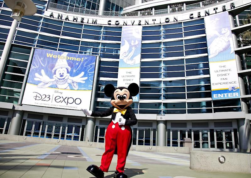 """FILE - In this Sept. 9, 2009 handout photo released by Disney, Mickey Mouse stands in front of the Anaheim Convention Center in preparation for the Disney D23 Expo in Anaheim, Calif. The Walt Disney Co. is cracking open the vault, rolling out the red carpet and pulling back the curtain for more than 45,000 expected fans at this weekend's D23 Expo, Aug. 9-11, 2013, a three-event celebration of all things Disney at the Anaheim Convention Center. On the animation front, the studio will showcase Walt Disney Animation Studios' computer-generated adventure """"Frozen"""" and Pixar's prehistoric comedy """"The Good Dinosaur"""" during a Friday presentation, as well as the """"Finding Nemo"""" sequel """"Finding Dory,"""" the manga-style Marvel adaptation """"Big Hero 6"""" and the new Mickey Mouse short film """"Get a Horse!"""" (AP Photo/Disney, Scott Brinegar, File)"""