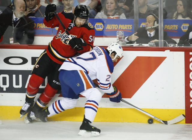Edmonton Oilers' Boyd Gordon, right, chases the puck as Calgary Flames' David Jones crashes down on him during the first period of an NHL hockey game Saturday, Nov. 16, 2013 in Calgary, Alberta. (AP Photo/The Canadian Press, Jeff McIntosh)
