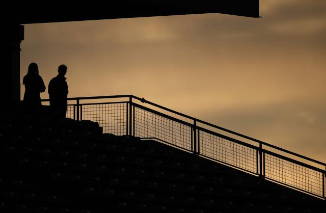 Two fans are silhouetted against the sky near sunset, during the fourth inning of a baseball game between the San Diego Padres and the Colorado Rockies on Friday, May 10, 2019, in Denver. (AP Photo/David Zalubowski)