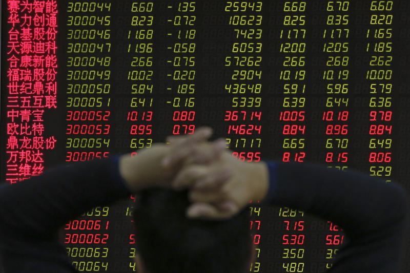 A man monitors shares prices at a brokerage house in Beijing, Tuesday, Jan. 22, 2019. Asian markets were mostly lower on Tuesday after the International Monetary Fund trimmed its global outlook for 2019 and 2020. This came after China said its economy grew at the slowest pace in 30 years. (AP Photo/Andy Wong)
