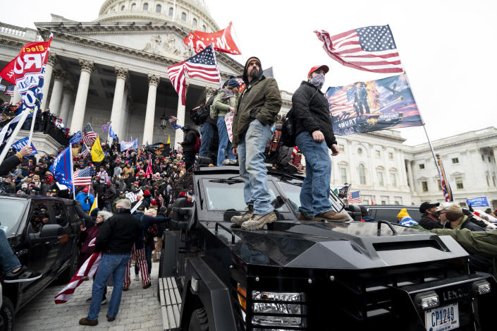 Trump supporters stand on the U.S. Capitol Police armored vehicle as others take over the steps of the Capitol as the Congress works to certify the electoral college votes. (Bill Clark/CQ-Roll Call, Inc via Getty Images)