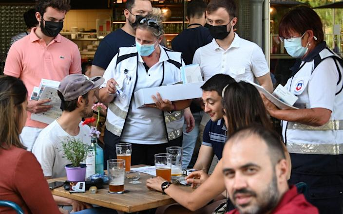 Anti-Covid mediators deliver hydroalcoholic solutions to customers on a bar terrace in Strasbourg, eastern France - Frederick Florin/AFP