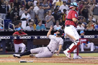 New York Yankees' Giancarlo Stanton, left, scores on a single past Miami Marlins catcher Sandy Leon during the eighth inning of a baseball game, Sunday, Aug. 1, 2021, in Miami. (AP Photo/Lynne Sladky)