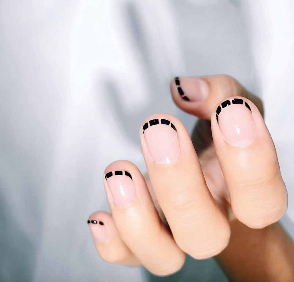If you're looking for a more minimalist version of stitched tips, here it is. Just trace a line of black along the edge of your nail, dip a toothpick into remover, and use it to create tiny cutouts.
