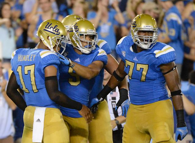 PASADENA, CA - AUGUST 31: Jordan Payton #9, Brett Hundley #17 and Torian White #77 of the UCLA Bruins celebrate a touchdown for a 23-13 lead during the third quarter against the Nevada Wolf Pack at Rose Bowl on August 31, 2013 in Pasadena, California. (Photo by Harry How/Getty Images)