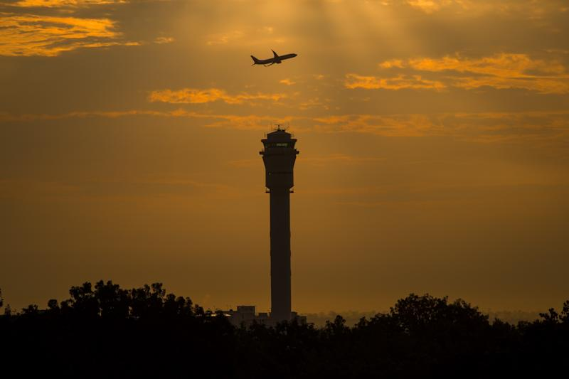 File Photo: An airplane flies past a control tower at Kuala Lumpur International Airport (KLIA) in Sepang, outside Kuala Lumpur on December 11, 2014. (Photo: MOHD RASFAN/AFP via Getty Images)