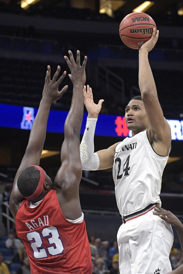 Cincinnati forward Kyle Washington (24) goes up for a shot in front of SMU forward Akoy Agau (23) during the second half of an NCAA college basketball quarterfinal game at the American Athletic Conference tournament Friday, March 9, 2018, in Orlando, Fla. Cincinnati won 61-51. (AP Photo/Phelan M. Ebenhack)