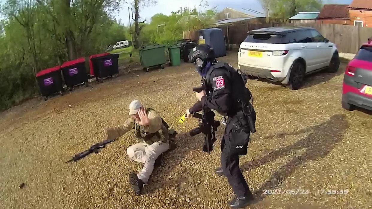 A police firearms officer runs to restrain paedophile Simon Tait. (SWNS)