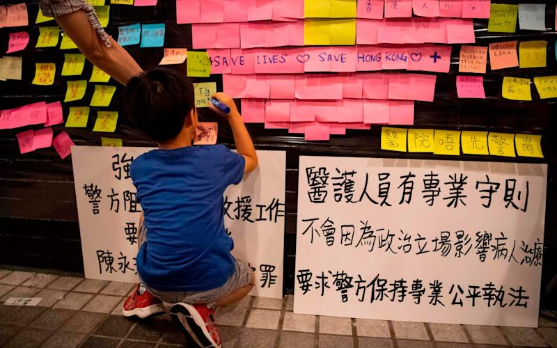 A boy writes on a Lennon Wall at a protest held by medics in the Central District of Hong Kong - AFP