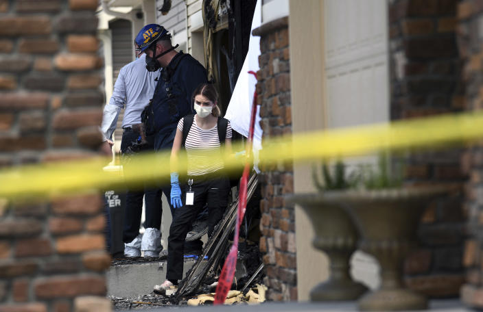 Investigators examine a house where five people were found dead after a fire in suburban Denver on Wednesday, Aug. 5, 2020. Three people escaped the fire by jumping from the home's second floor. Investigators believe the victims were a toddler, an older child and three adults. Authorities suspect was intentionally set. Witnesses told firefighters that three people on the second floor of the burning home jumped to safety. A fire department spokesman said the fire's heat pushed back a police officer trying to rescue the people who were on the home's first floor. (AP Photo/Thomas Peipert)