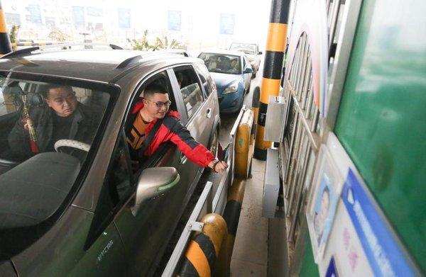 A driver is paying highway tolls using the Wechat payment service in Guiyang West Toll Station on January 1, 2019.