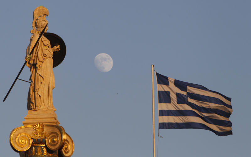 The moon rises behind the 19th century statue of the ancient goddess Athena as a Greek flag billows at the Athens Academy in Athens, Tuesday, July 12, 2011. Greece's finance minister on Tuesday said the country wants the European Union to conclude a second rescue loan deal by the end of August, as volatile international markets fretted over the vulnerability of other eurozone members to the escalating debt crisis.  (AP Photo/Thanassis Stavrakis)