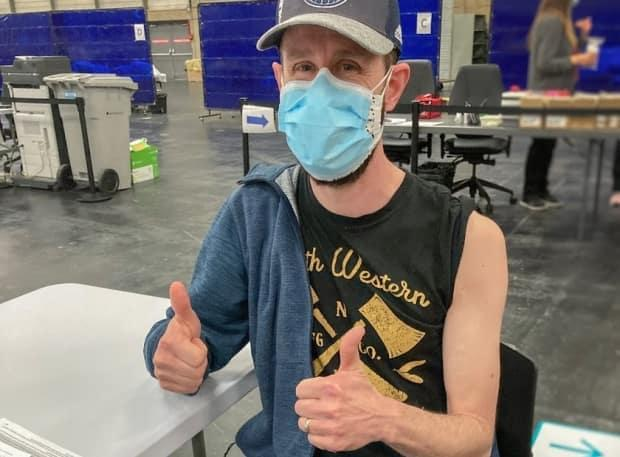 Kalvin Clauer, 40, gives a thumbs up after receiving the COVID-19 vaccine at the Edmonton Expo Centre mass-immunization site on Tuesday.  (AHS - image credit)