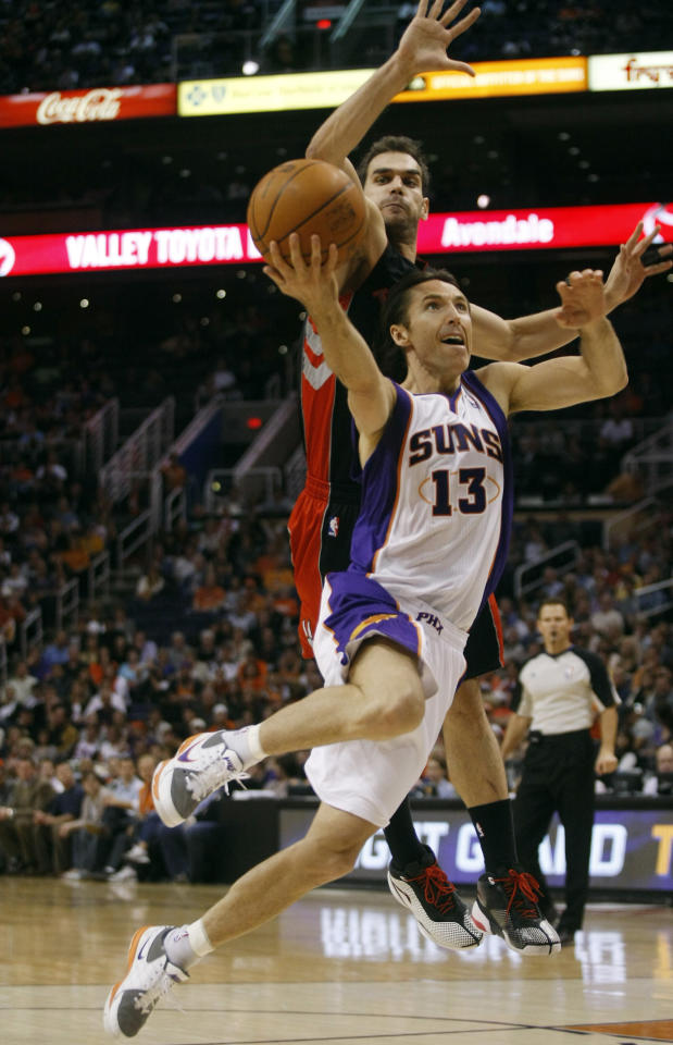 Toronto Raptors point guard Calderon blocks the shot of Phoenix Suns point guard Nash in the third quarter of an NBA basketball game. 2011. Reuters/ Images