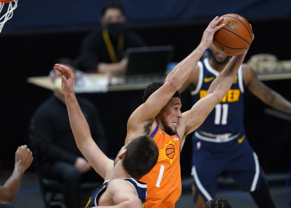 Phoenix Suns guard Devin Booker pulls in a rebound as Denver Nuggets center Nikola Jokic defends during the second half of an NBA basketball game Friday, Jan. 1, 2021, in Denver. The Suns won 106-103. (AP Photo/David Zalubowski)