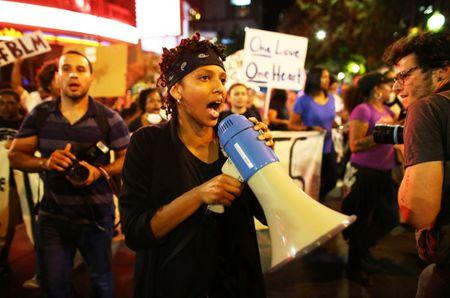 A protester speaks through a megaphone during another night of protests over the police shooting of Keith Scott in Charlotte, North Carolina, U.S. September 23, 2016.  REUTERS/Mike Blake
