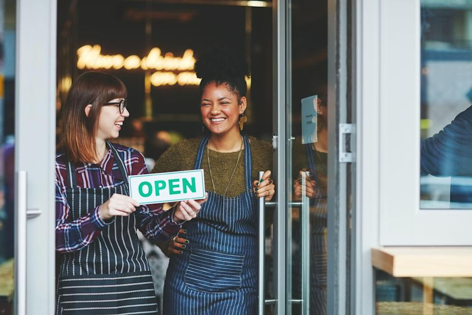 Shot of two young women holding up an open sign in their coffee shop