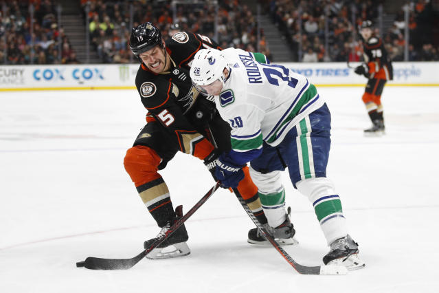 Vancouver Canucks' Antoine Roussel, right, of France, hits the puck away from Anaheim Ducks' Ryan Getzlaf during the second period of an NHL hockey game Wednesday, Nov. 21, 2018, in Anaheim, Calif. (AP Photo/Jae C. Hong)