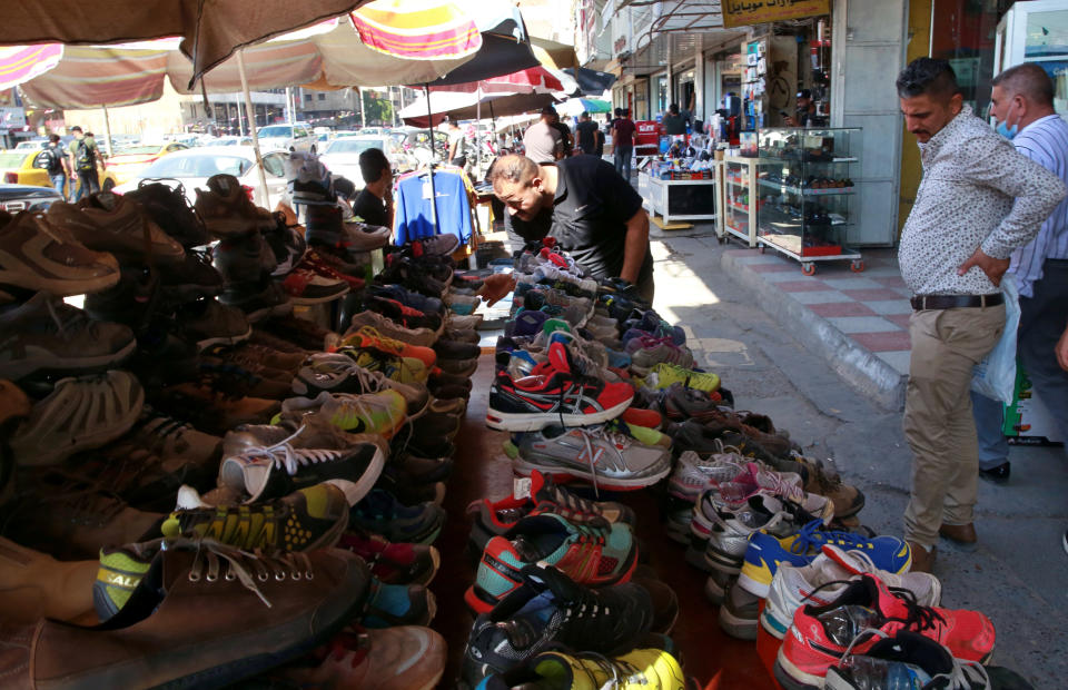 People shop for used shoes at the used-clothes market in Baghdad, Iraq, Tuesday, Oct. 20, 2020. Iraq is in the throes of an unprecedented liquidity crisis, as the cash-strapped state wrestles to pay public sector salaries and import essential goods while oil prices remain dangerously low. (AP Photo/Khalid Mohammed)