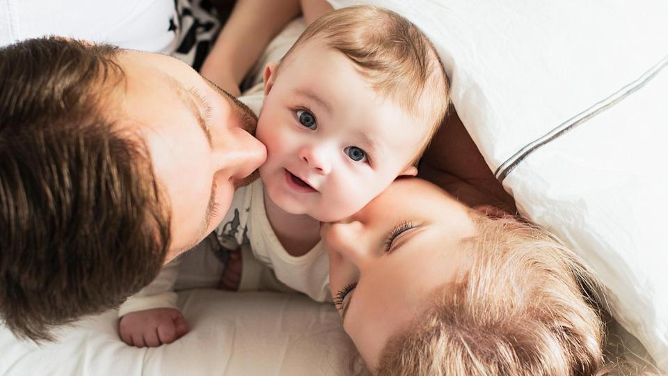 Parents kissing their baby - Image.