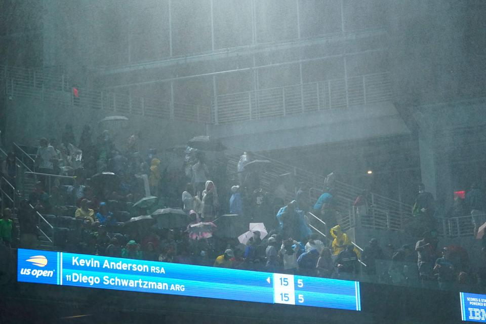 Rain falls into Louis Armstrong Stadium from the openings along the side during the match between Diego Schwartzman and Kevin Anderson.