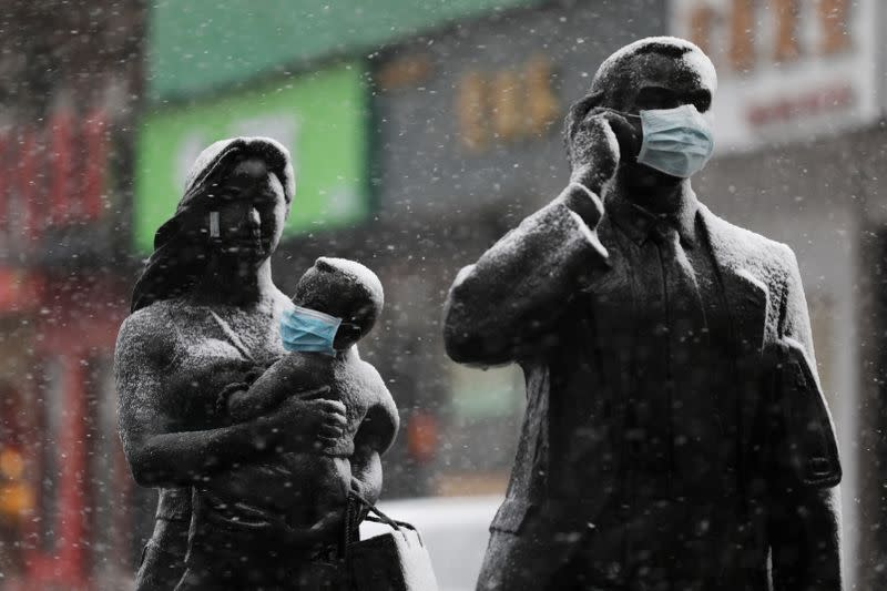 Statues with face masks on are seen amid snow in Wuhan, the epicentre of the novel coronavirus outbreak