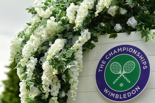 A Wimbledon logo fringed by flowers at the All England Club (AFP Photo/Glyn KIRK )