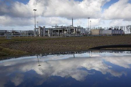 A view of a gas production plant is reflected in the roof of a car in 't Zand in Groningen