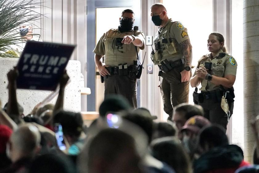Maricopa County Sheriff's Deputies stand at the door of the Maricopa County Recorder's Office as President Donald Trump supporters rally outside, Wednesday, Nov. 4, 2020, in Phoenix. (AP Photo/Matt York)