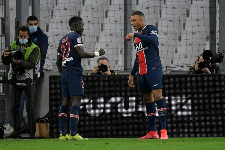 Kylian Mbappe (R) celebrates with Idrissa Gana Gueye after bursting through to put Paris Saint-Germain in front against Marseille