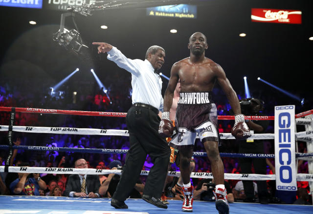 The referee sends Terence Crawford, right, to a neutral corner after Crawford knocked down Jeff Horn, of Australia, during a welterweight title boxing match, Saturday, June 9, 2018, in Las Vegas. (AP Photo/John Locher)
