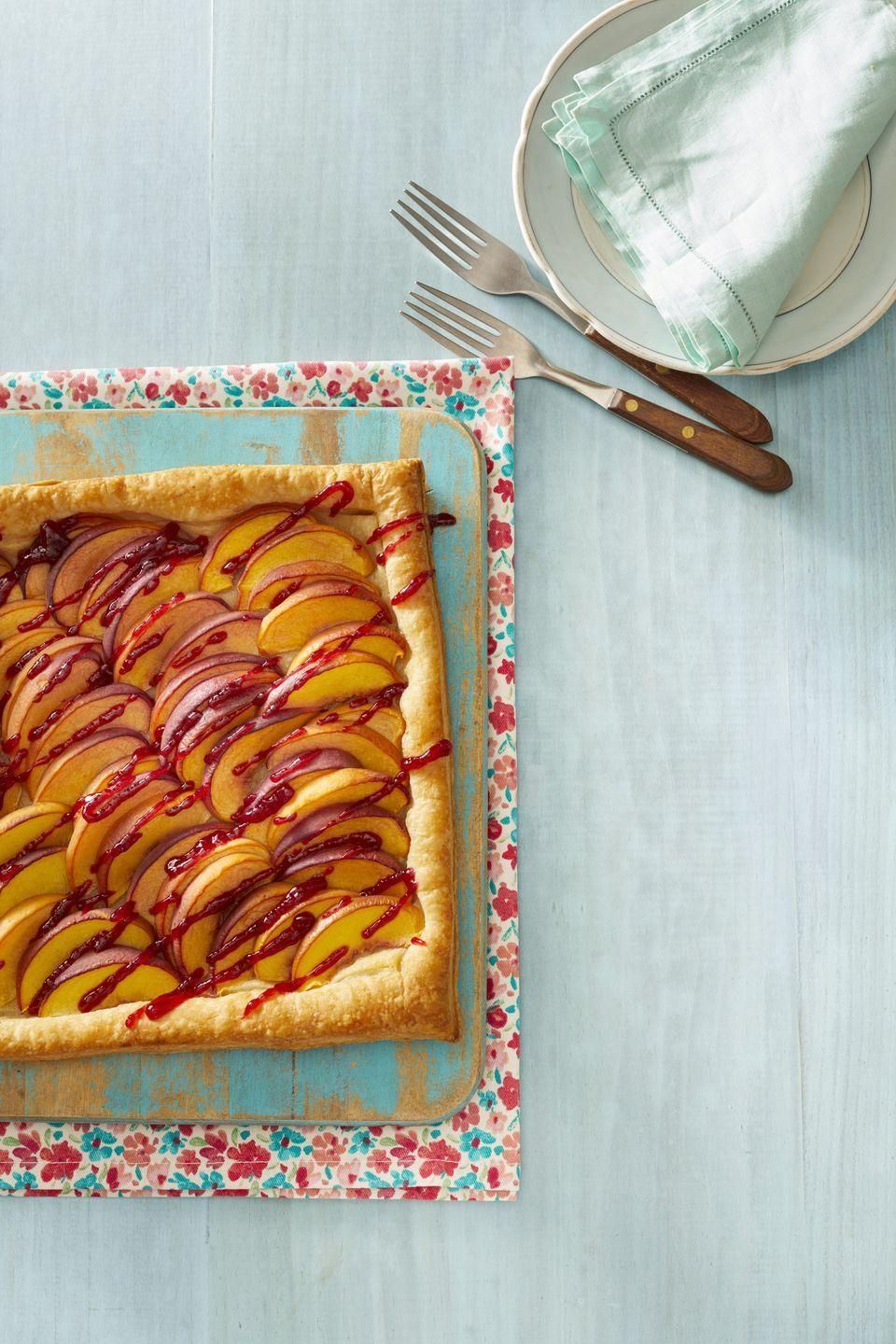"""<p>Puff pastry is the secret to this simple but stunning tart. The raspberry drizzle on top makes it extra special!</p><p><a href=""""https://www.thepioneerwoman.com/food-cooking/recipes/a32096774/peach-melba-tart-recipe/"""" rel=""""nofollow noopener"""" target=""""_blank"""" data-ylk=""""slk:Get Ree's recipe."""" class=""""link rapid-noclick-resp""""><strong>Get Ree's recipe.</strong></a></p><p><a class=""""link rapid-noclick-resp"""" href=""""https://go.redirectingat.com?id=74968X1596630&url=https%3A%2F%2Fwww.walmart.com%2Fsearch%2F%3Fquery%3Dpioneer%2Bwoman%2Bcutting%2Bboard&sref=https%3A%2F%2Fwww.thepioneerwoman.com%2Ffood-cooking%2Frecipes%2Fg36382592%2Fpeach-desserts%2F"""" rel=""""nofollow noopener"""" target=""""_blank"""" data-ylk=""""slk:SHOP CUTTING BOARDS"""">SHOP CUTTING BOARDS</a></p>"""