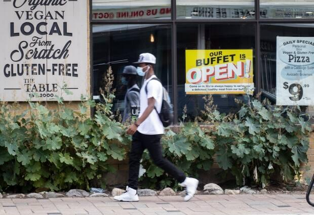 A pedestrian in a mask walks past an Ottawa restaurant's sign advertising that its buffet has reopened on Aug. 27, 2021, during the COVID-19 pandemic. (Trevor Pritchard/CBC - image credit)