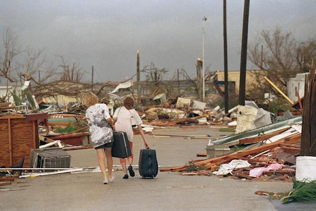 <p>Joan Wallach, left, and her daughter Brenda, right, walk through the debris that was the Royal Palm Trailer Court in Homestead, Fla., Aug. 25, 1992, carrying the only possessions they could salvage from the trailer they lived in before Hurricane Andrew hit the South Florida city. (AP Photo/Lynne Sladky) </p>
