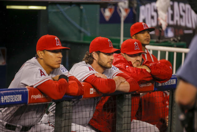 Los Angeles Angels players watch Kansas City Royals players celebrate following Game 3 of baseball's AL Division Series in Kansas City, Mo., Sunday, Oct. 5, 2014. The Kansas City Royals defeated the Los Angeles Angels 8-3 to sweep the series. (AP Photo/Travis Heying)