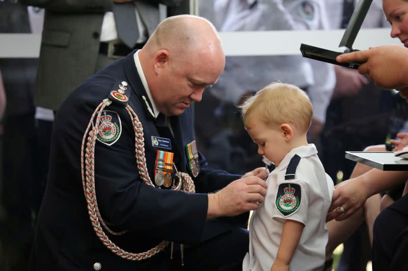 RFS Commissioner Shane Fitzsimmons presents a posthumous Commendation for Bravery and Service to the son of late RFS volunteer Keaton in Buxton