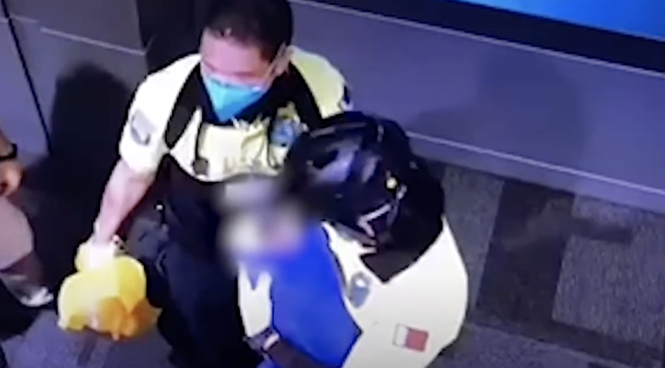 Pictured are paramedics coddling a newborn baby in a blue blanket after she was found in a bin at an airport in Doha.