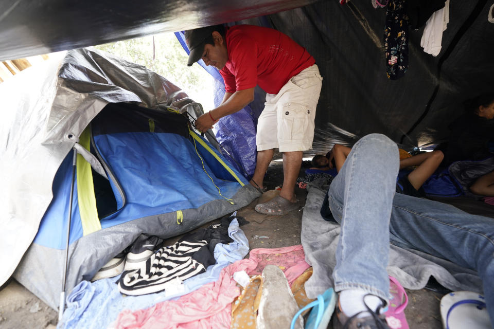 Jose Rodriguez, of Honduras closes is tent at a makeshift camp for migrants near the U.S.-Mexico border Friday, May 14, 2021, in Reynosa, Mexico. ing the heart-wrenching decision to separate from their children and send them into the U.S. alone. Many families with kids older than six have been quickly expelled from the country under federal pandemic-related powers that don't allow migrants to seek asylum. (AP Photo/Gregory Bull)