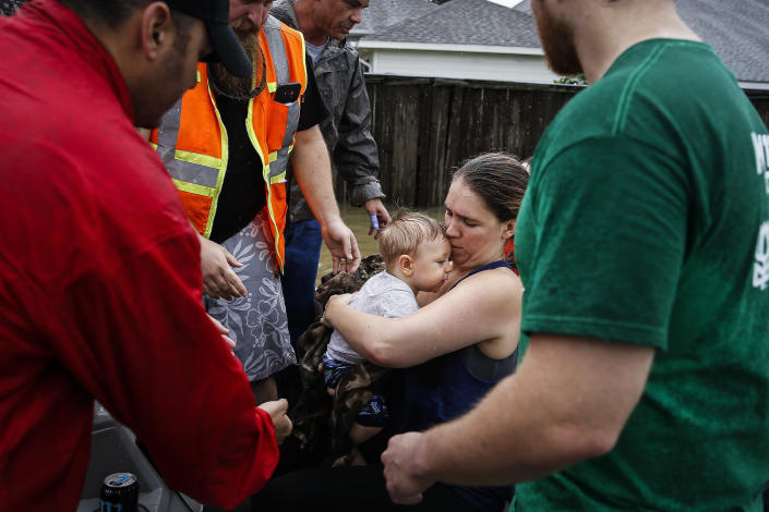 <em>Lauren Durst holds onto her ten-month-old son, Wyatt Durst, as they evacuate from the Savannah Estates neighbourhood as Addicks Reservoir nears capacity (AP)</em>