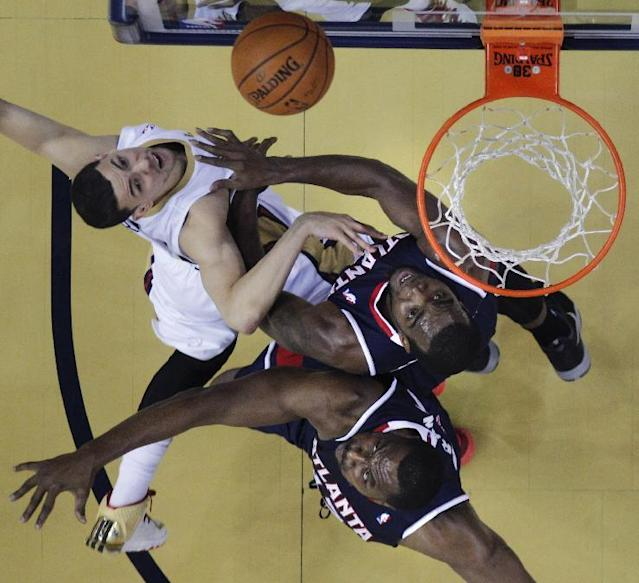 New Orleans Pelicans shooting guard Austin Rivers, left, goes to the basket against Atlanta Hawks power forward Paul Millsap, top right, and power forward Elton Brand in the first half of an NBA basketball game in New Orleans, Wednesday, Feb. 5, 2014. (AP Photo/Gerald Herbert)